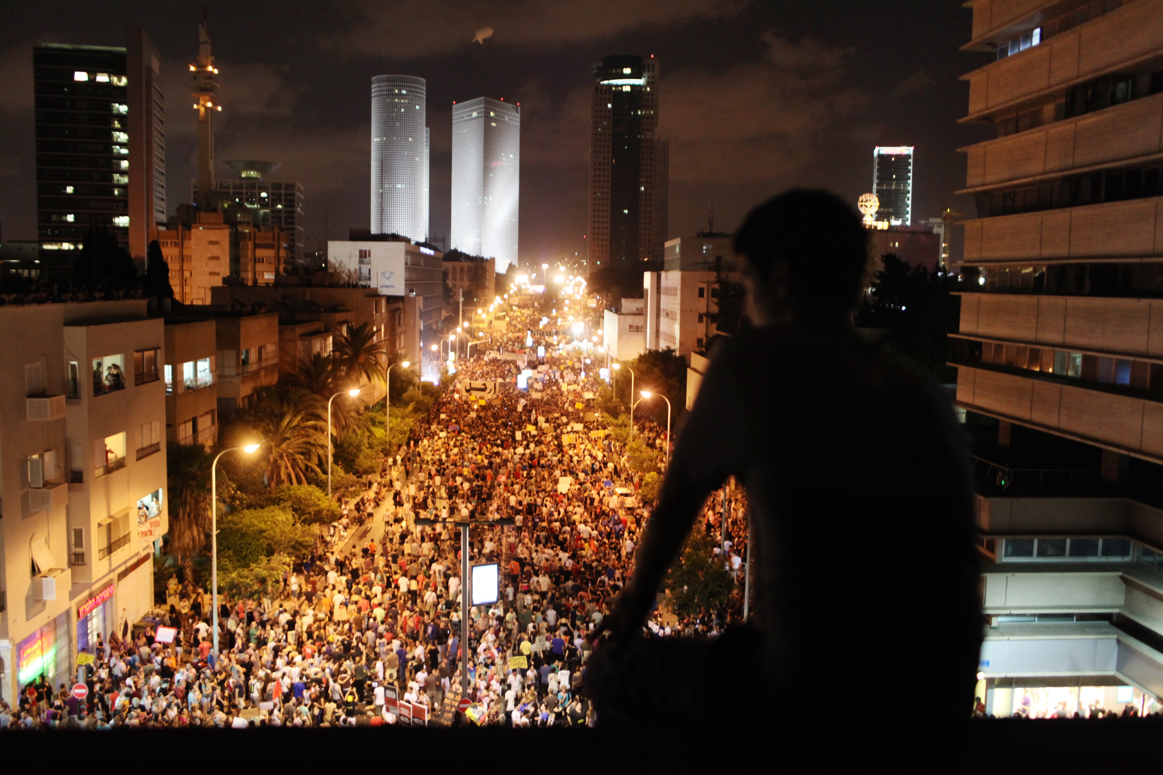 Man overlooking crowd on streets