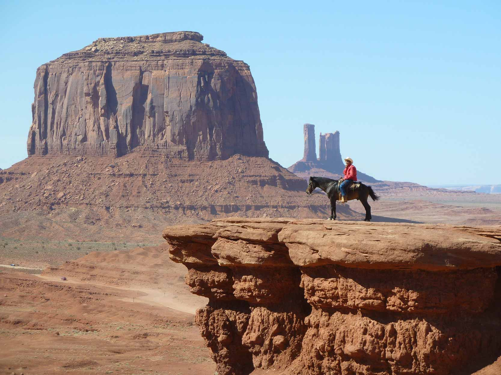 A person with a wide-brim had sits astride a horse on a cloudless day by a dusty canyon.